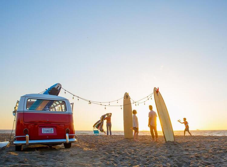 van and surfboards on beach
